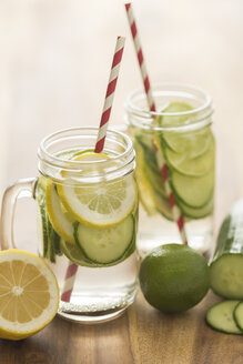 Glasses of infused water with lime, lemon, cucumber and ice cubes - JUNF00706