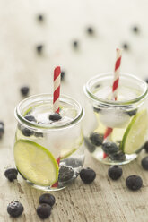 Glasses of infused water with lime, blueberries and ice cubes - JUNF00709