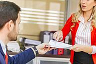 Secretary handing over document to businessman in office - ZEDF00452