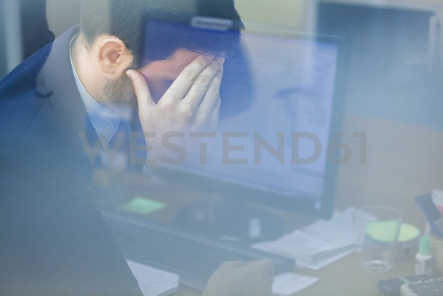 Young businessman in office with head in hand - ZEDF00455