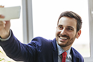 Happy young businessman taking a selfie - ZEDF00458