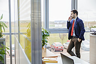 Young businessman on cell phone in office - ZEDF00461