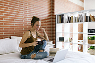 Woman sitting on bed drinking coffee, using laptop and reading book - VABF00883