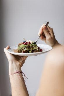 Woman eating vegan matcha cake - VABF00895