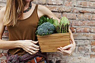 Woman holding basket with fresh vegetables - VABF00904