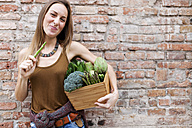 Smiling woman holding basket with fresh vegetables - VABF00907