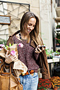Smiling woman with flowers and cell phone outdoors - VABF00910