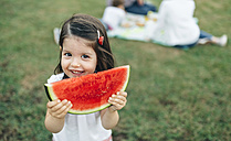 Portrait of smiling girl holding watermelon slice with her family in background - DAPF00522