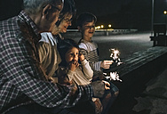 Grandparents with grandchildren holding sparklers at night - DAPF00528