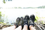 Legs of couple on a hiking tour resting at a lake - HAPF01182