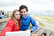Young couple on a hiking tour taking a selfie at rest area - HAPF01194