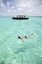 Maldives, Maafushi island, woman snorkeling - DSGF01240