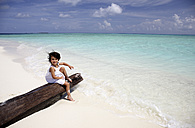 Maldives, girl sitting on a log on a beach - DSGF01243