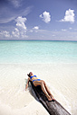 Maldives, woman sunbathing on a log on a beach - DSGF01246