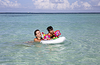 Maldives, Gulhi, mother and daughter playing with an inflatable airbed in shallow water - DSGF01252