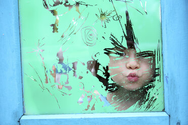 Girl looking through the glass of an old window - DSGF01255