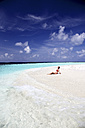 Maldives, woman sitting on beach at shallow water - DSGF01267