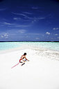 Maldives, woman on beach at shallow water - DSGF01270