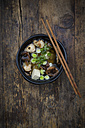 Bowl of miso soup with organic tofu, shitake mushrooms, leek and parsley on dark wood - LVF05697