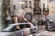 Young woman in a cafe looking out of window - UUF09484