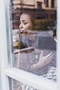 Young woman in a cafe looking out of window - UUF09487