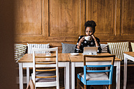 Young woman with tablet drinking coffee in a cafe - UUF09499