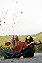 Two best friends sitting on country road throwing confetti in the air - KKAF00178