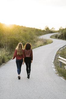 Back view of two friends walking side by side on empty road - KKAF00181