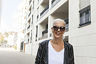 Portrait of smiling woman wearing sunglasses and leather jacket - JUNF00722