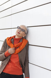 Portrait of fashionable mature woman leaning against white wall - JUNF00746