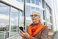 Portrait of fashionable mature woman looking at cell phone - JUNF00749