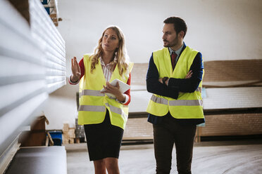 Man and woman in warehouse supervising stock - ZEDF00462