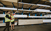 Man and woman in warehouse supervising stock - ZEDF00465
