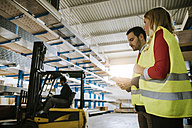 Man and woman wearing reflective vests in warehouse - ZEDF00468