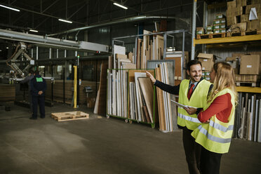 Smiling man and woman wearing reflective vests in warehouse - ZEDF00471