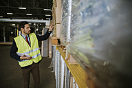 Man in warehouse supervising stock - ZEDF00474
