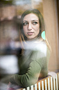 Young woman sitting in coffee shop, looking through window - TAMF00891