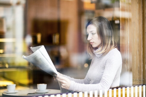 Young woman sitting in coffee shop, reading newspaper - TAMF00894