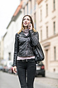 Young woman in the street using smart phone - TAMF00897