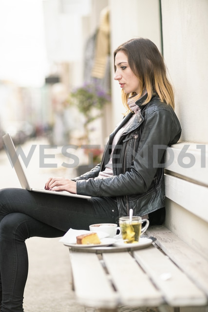 Young woman sitting on outdoor bench using laptop - TAMF00900 - A. Tamboly/Westend61