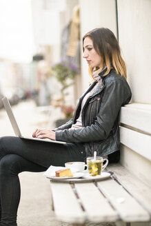 Young woman sitting on outdoor bench using laptop - TAMF00900
