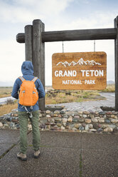 USA, Wyoming, back view of man with backpack standing at entrance of Grand Teton National Park - EPF00194