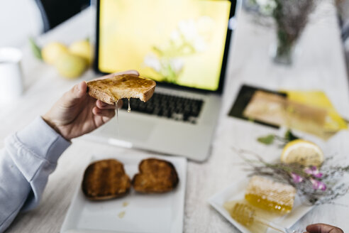 Man's hand holding bitten toast with dripping honey at his workplace, close-up - JRFF01108