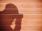 Shadow of a man taking picture with camera on a wall - KRPF02070
