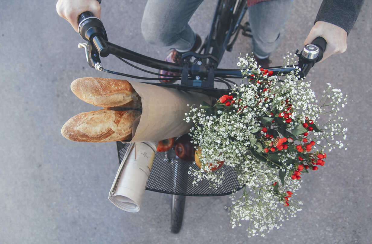 Man with apples, bouquet of flowers, newspaper and baguettes in bicycle basket - RTBF00557 - Retales Botijero/Westend61