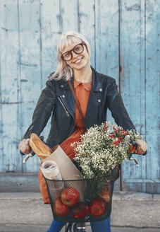 Smiling young woman with groceries on bicycle - RTBF00563