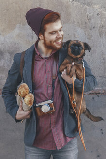 Smiling young man holding dog - RTBF00569