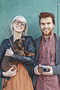 Portrait of smiling young couple holding a dog - RTBF00572