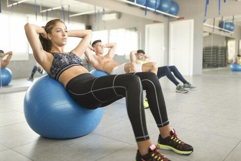 Woman exercising abs on gym ball - JASF01380