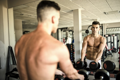 Man lifting weights in front of mirror - JASF01392